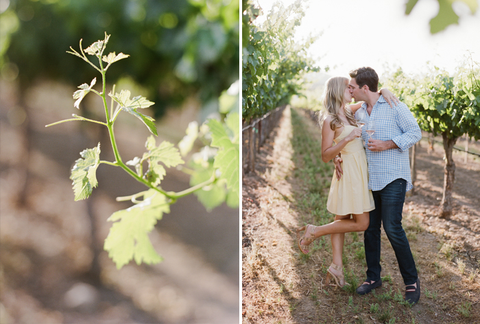 A couple shares a kiss with glasses of wine in a Napa Valley vineyard   during an engagement session with Sylvie Gil.