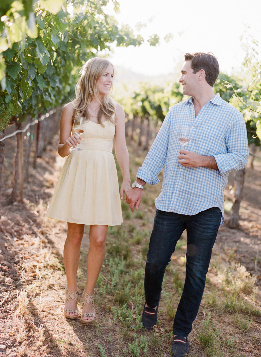A couple holds hands and walks through a Napa Valley vineyard  during an engagement session with Sylvie Gil.
