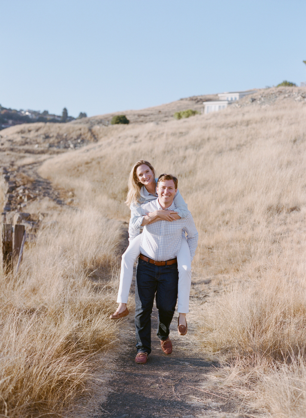 Man carries his fiancee in a piggyback ride through the hills of Tiburon  during an engagement session with Sylvie Gil.