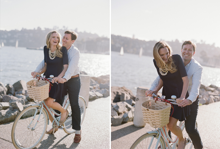 Cute couple joke and ride a bicycle together on a boardwalk in Tiburon during an engagement session with Sylvie Gil.