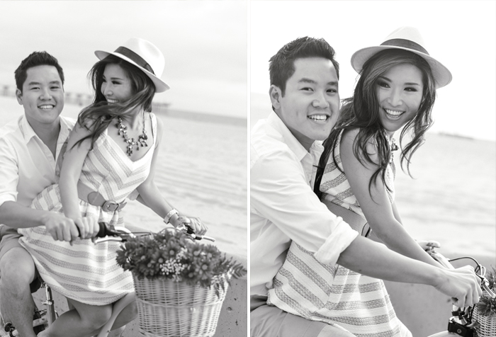 Black & white film engagement session with Sylvie Gil - couple rides a bicycle together down Hermosa Beach boardwalk.