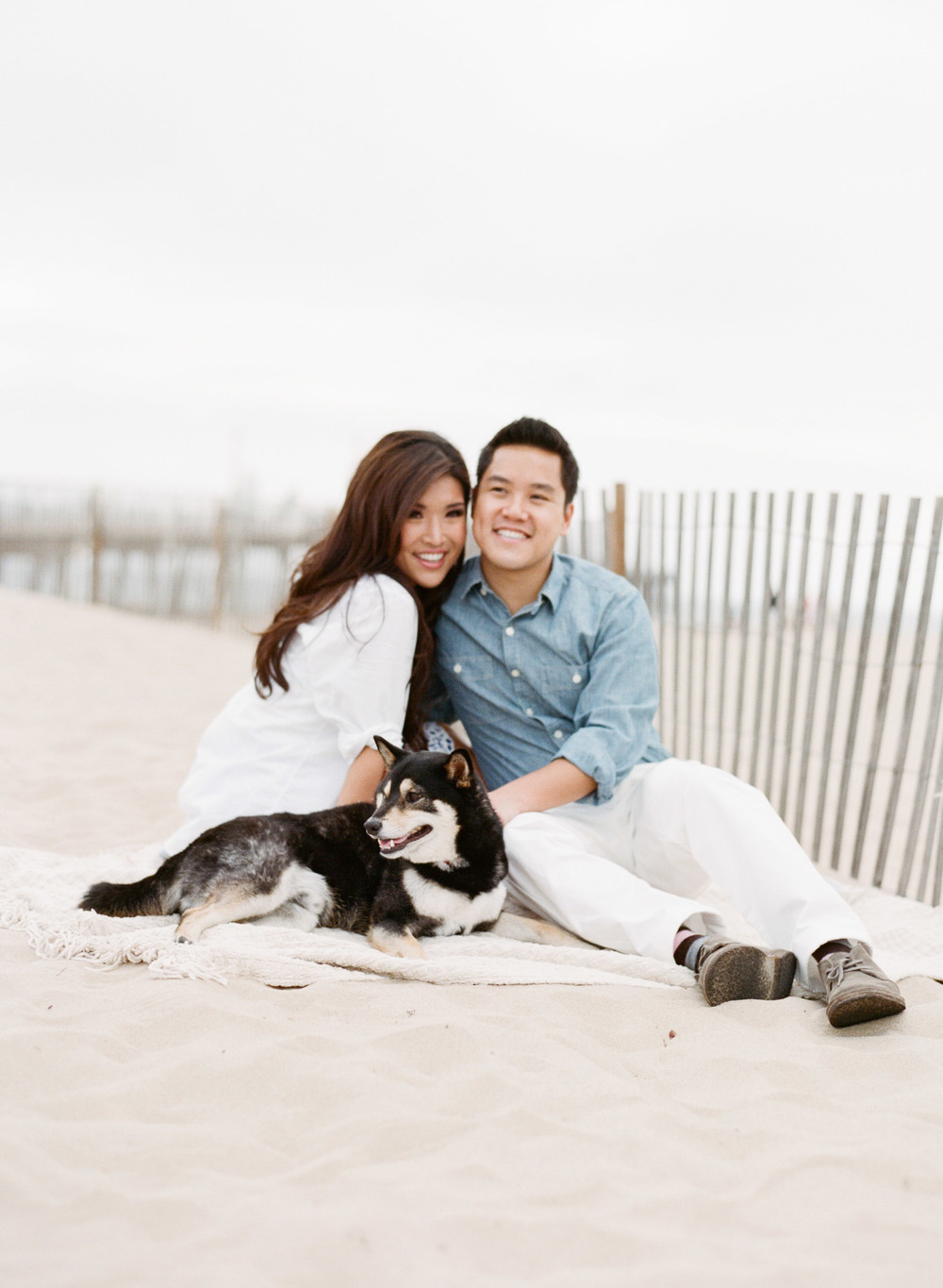 Couple with their cute dog in the sand at Hermosa Beach during an engagement shoot with Sylvie Gil.