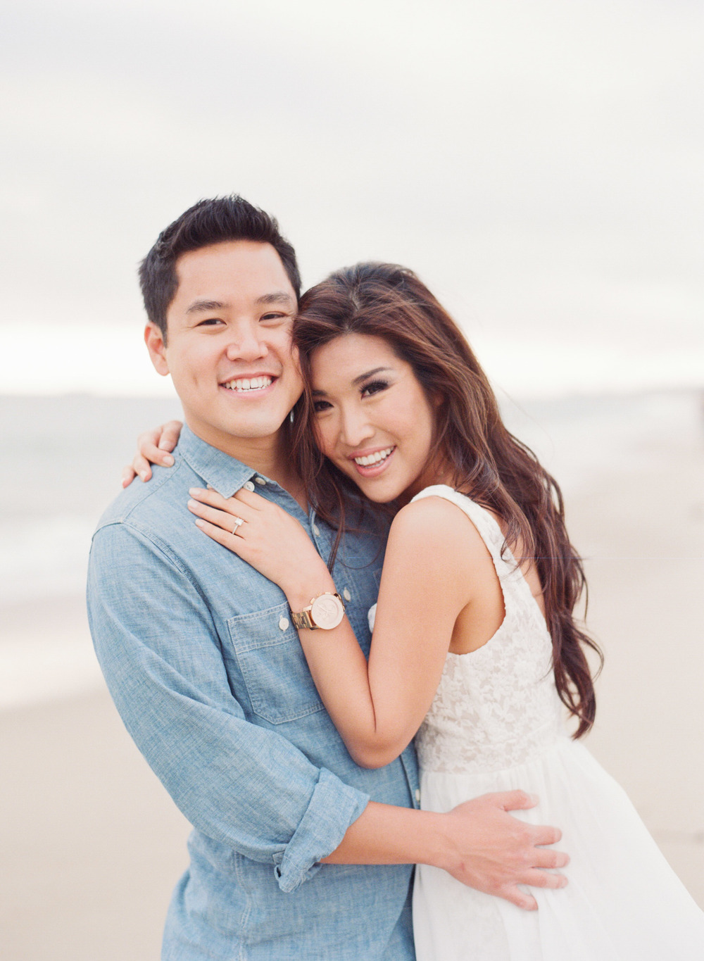Smiling couple embraces on Hermosa Beach during an engagement shoot with Sylvie Gil.