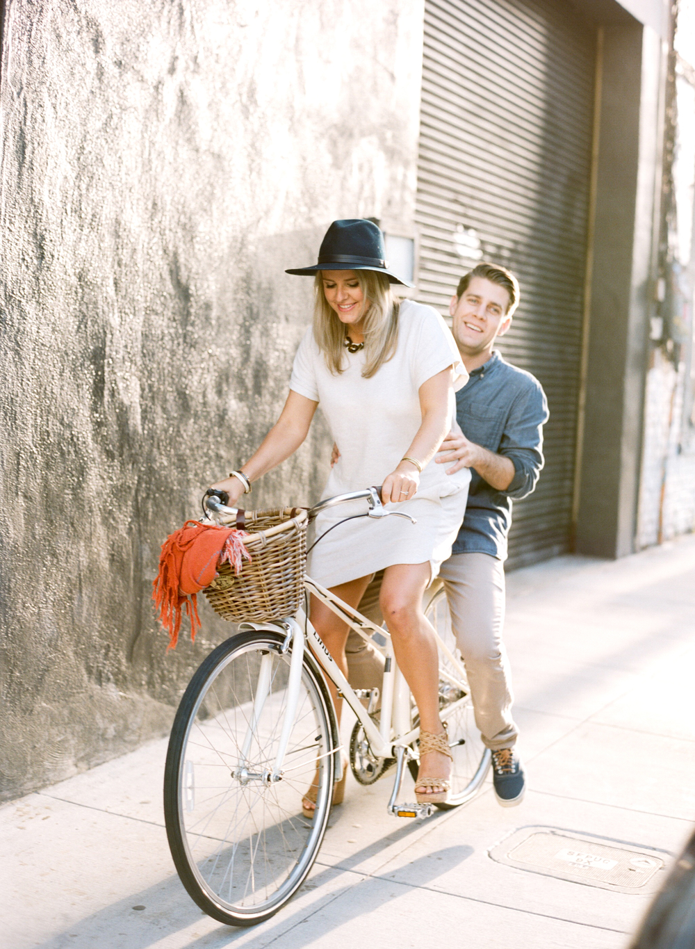 Couple rides a bike together down an alley in San Francisco during an engagement shoot with Sylvie Gill.