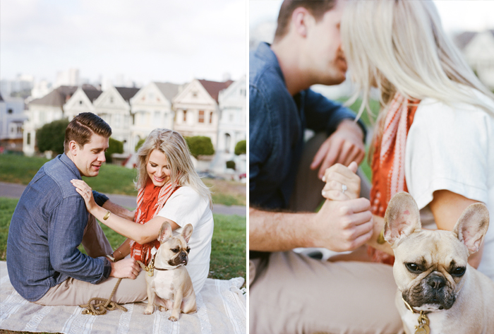 A couples sits on the grass at Alamo Square Park with their French bulldog during an engagement shoot with Sylvie Gil