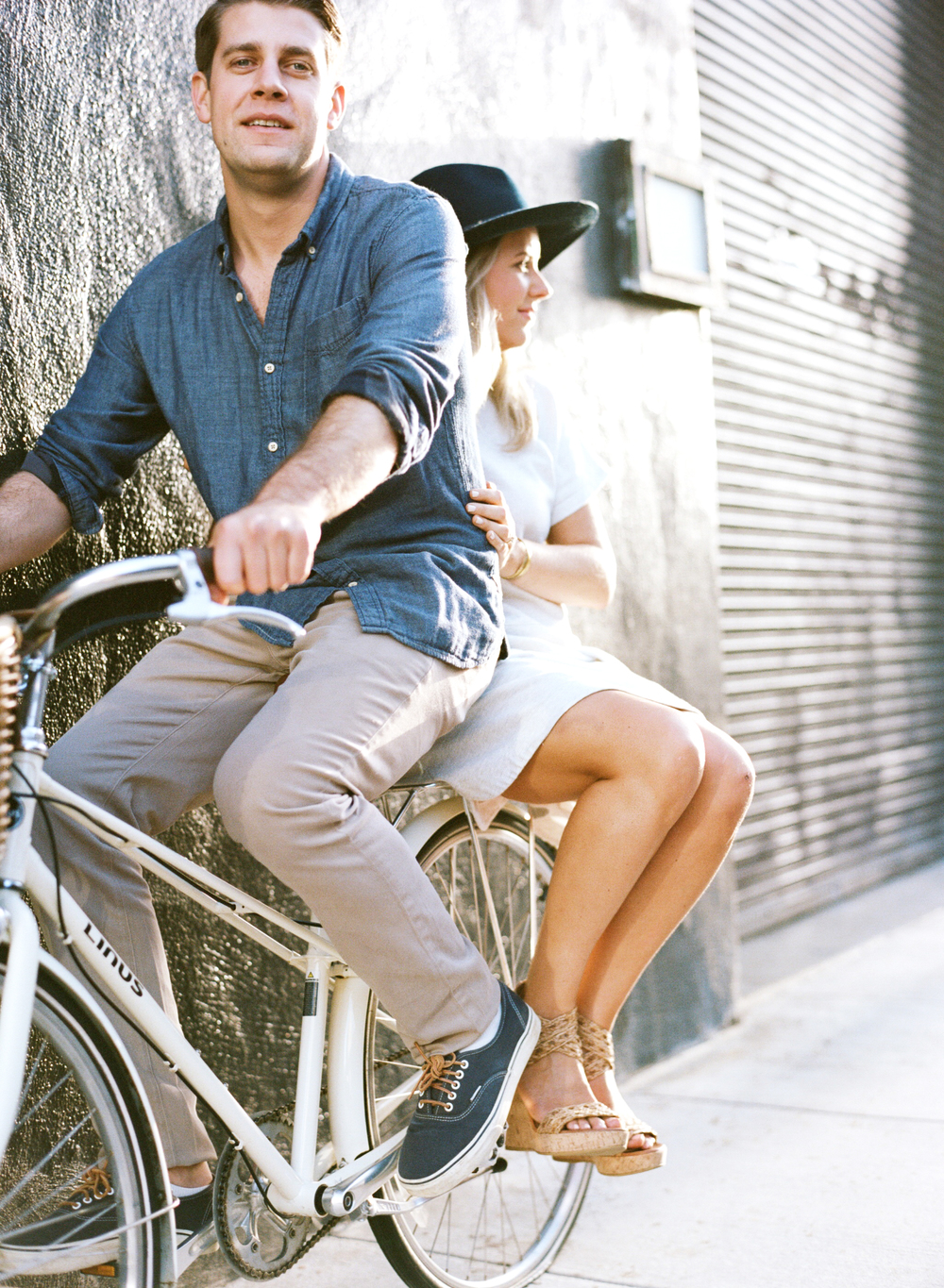 A groom-to-be rides a bicycle while his fiancee sits in back during an engagement session with Sylvie Gil.