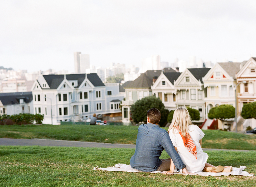A couple look out at the San Francisco skyline during an engagement session with Sylvie Gil.