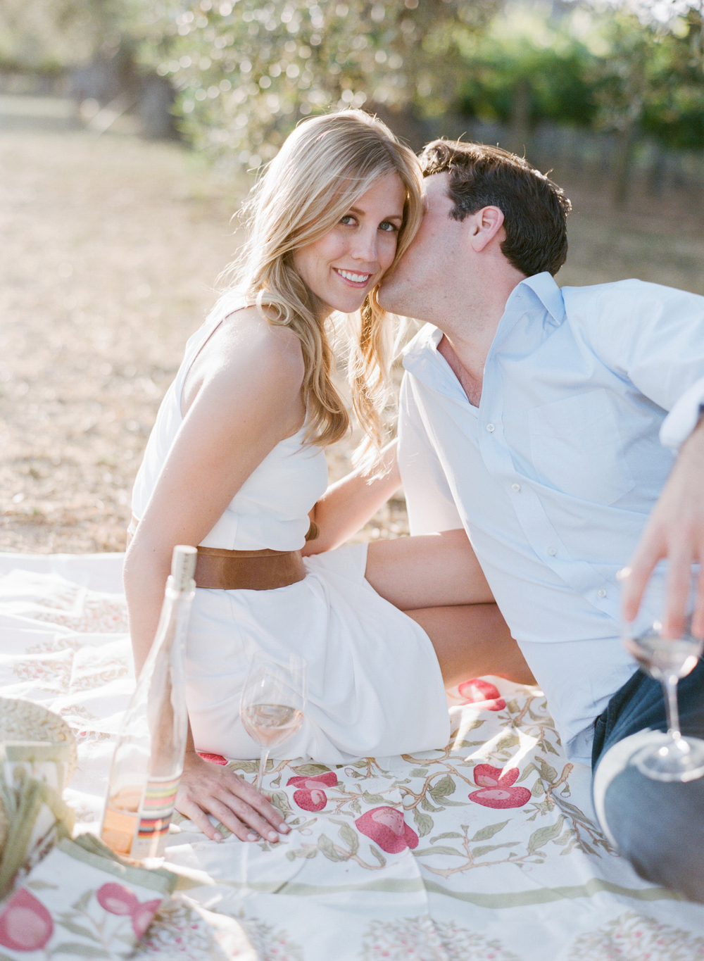 A groom-to-be steals a kiss with his fiancee as they picnic in a Napa Valley vineyard  during an engagement session with Sylvie Gil.