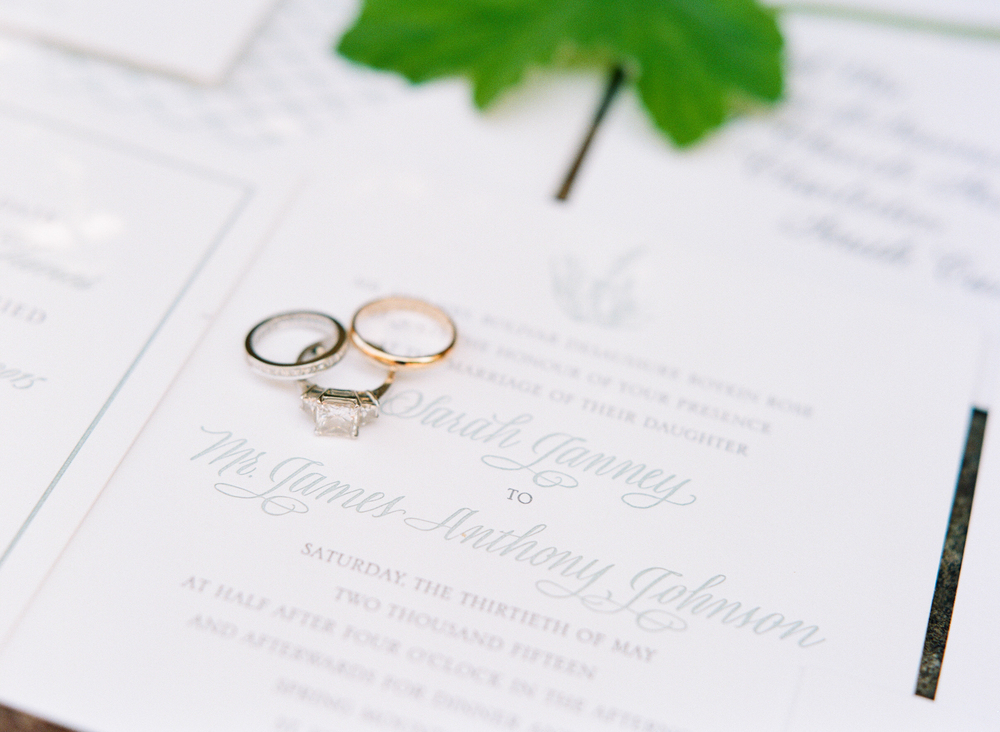 Sarah and James' rings sit atop their beautiful invitation suite; photo by Sylvie Gil.