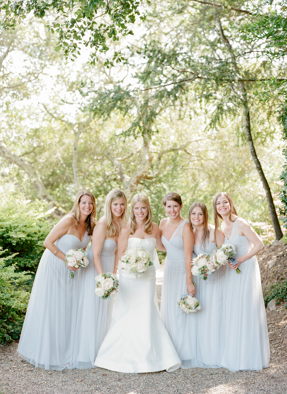Sarah and her bridesmaids, dressed in pastel blue, lean in close for a photograph, by Sylvie Gil
