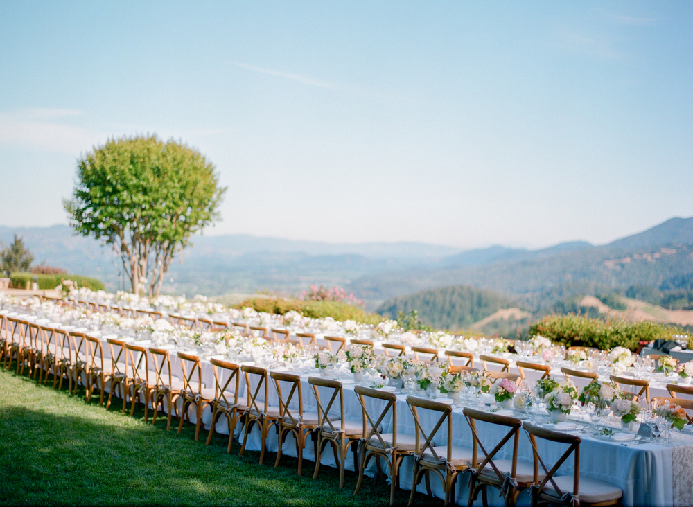 Long, elegantly decorated tables at the reception look out over vast Northern California vineyards; photo by Sylvie Gil