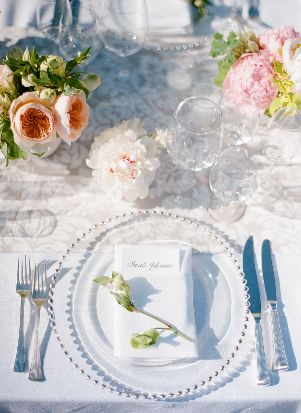 Calligraphied place holders and blushing pastel florals decorate each place setting; photo by Sylvie Gil