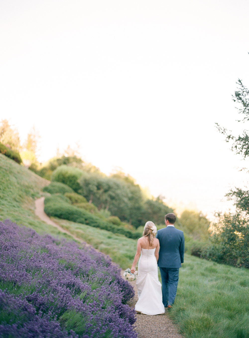 Newlyweds find a moment of calm after the ceremony, walking hand in hand for a couple portrait by a lavender field; photo by Sylvie GIl
