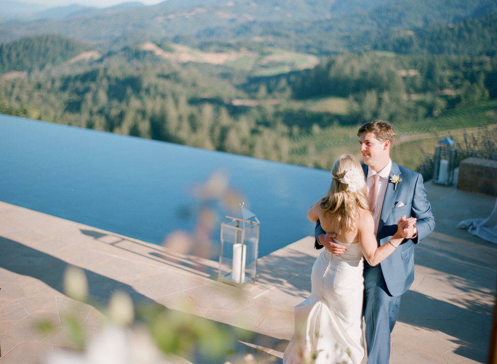 James and Sarah share their first dance on a patio overlooking verdant Napa vineyards; photo by Sylvie Gil