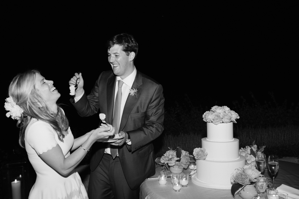 Sarah and James share a sweet, silly moment over cake cutting; photo by Sylvie Gil