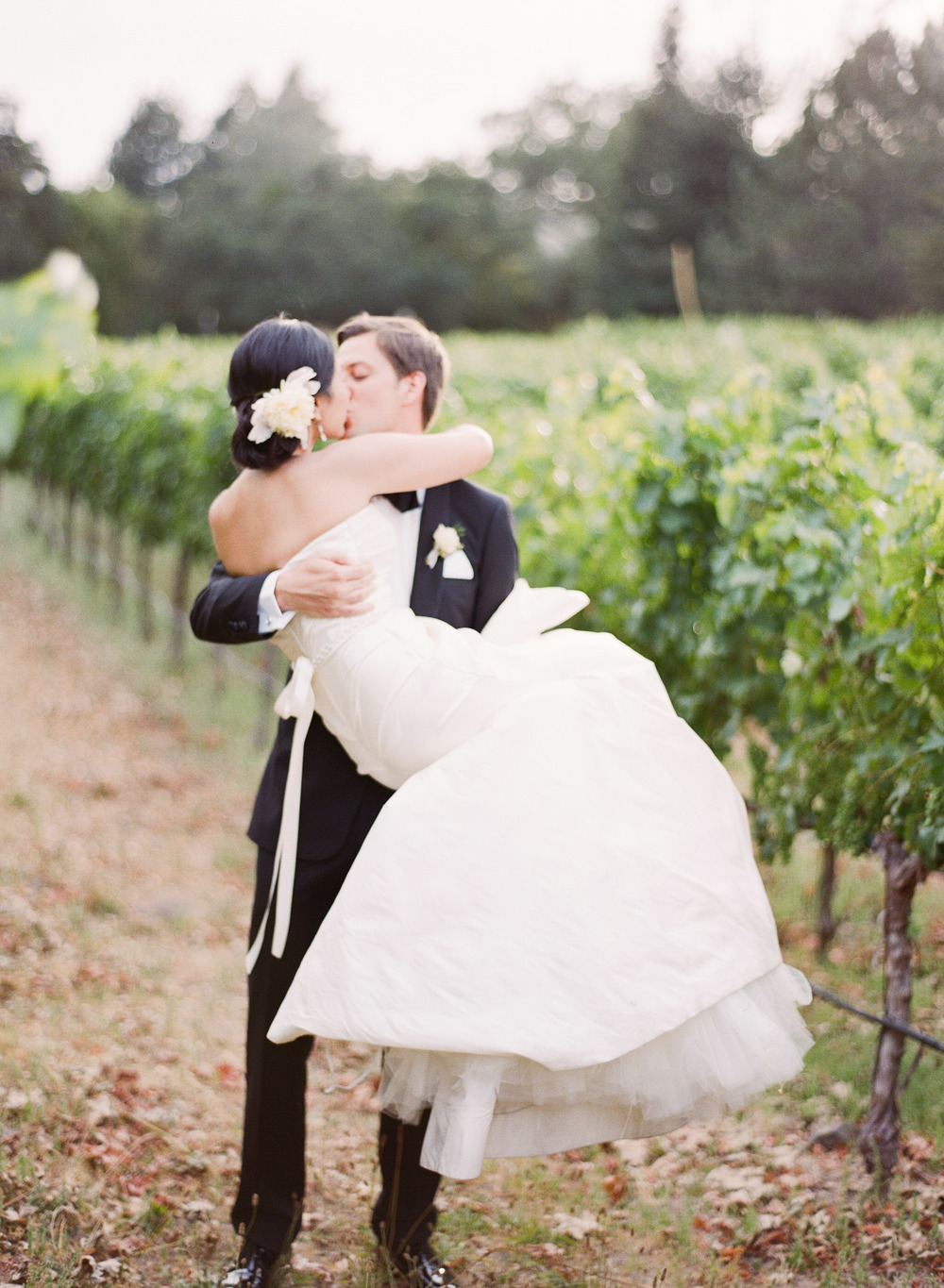 Peter lifts up his bride for a kiss in a Napa vineyard during a couple session with Sylvie Gil