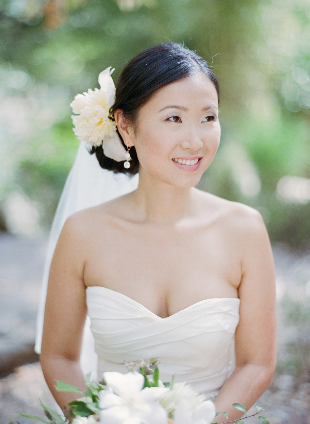 A glowing bride, dressed in an Oscar de la Renta gown, poses before her Napa Valley wedding; photo by Sylvie Gil