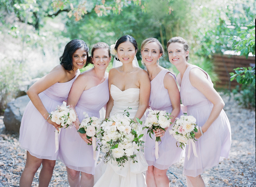 The bridesmaids, dressed in lavender one-shoulder gowns lean in for a photograph with the bride; photo by Sylvie Gil