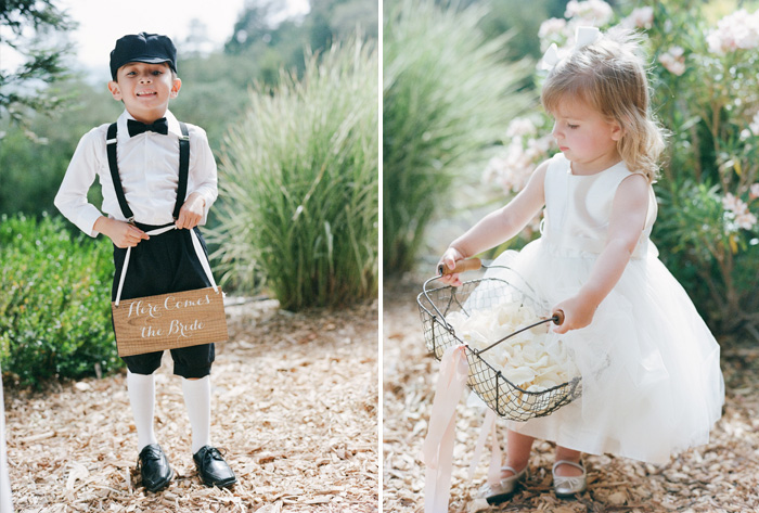 The dapper ringbearer holds a sign; an adorable flower girl holds a wire basket of flower petals; photo by Sylvie Gil