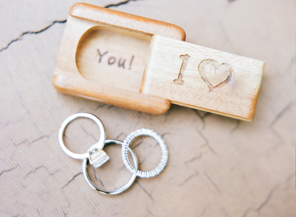 An adorable wooden ring box holds the ceremony rings for Di + Peter; photo by Sylvie Gil