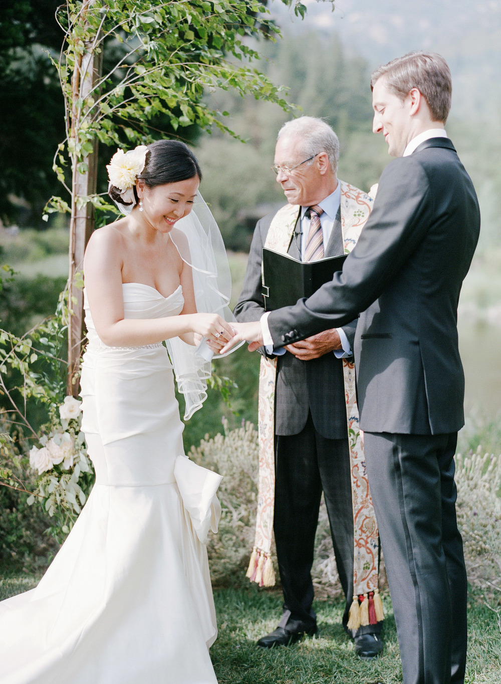 The bride and groom exchange rings during their Napa Valley wedding ceremony; photo by Sylvie Gil