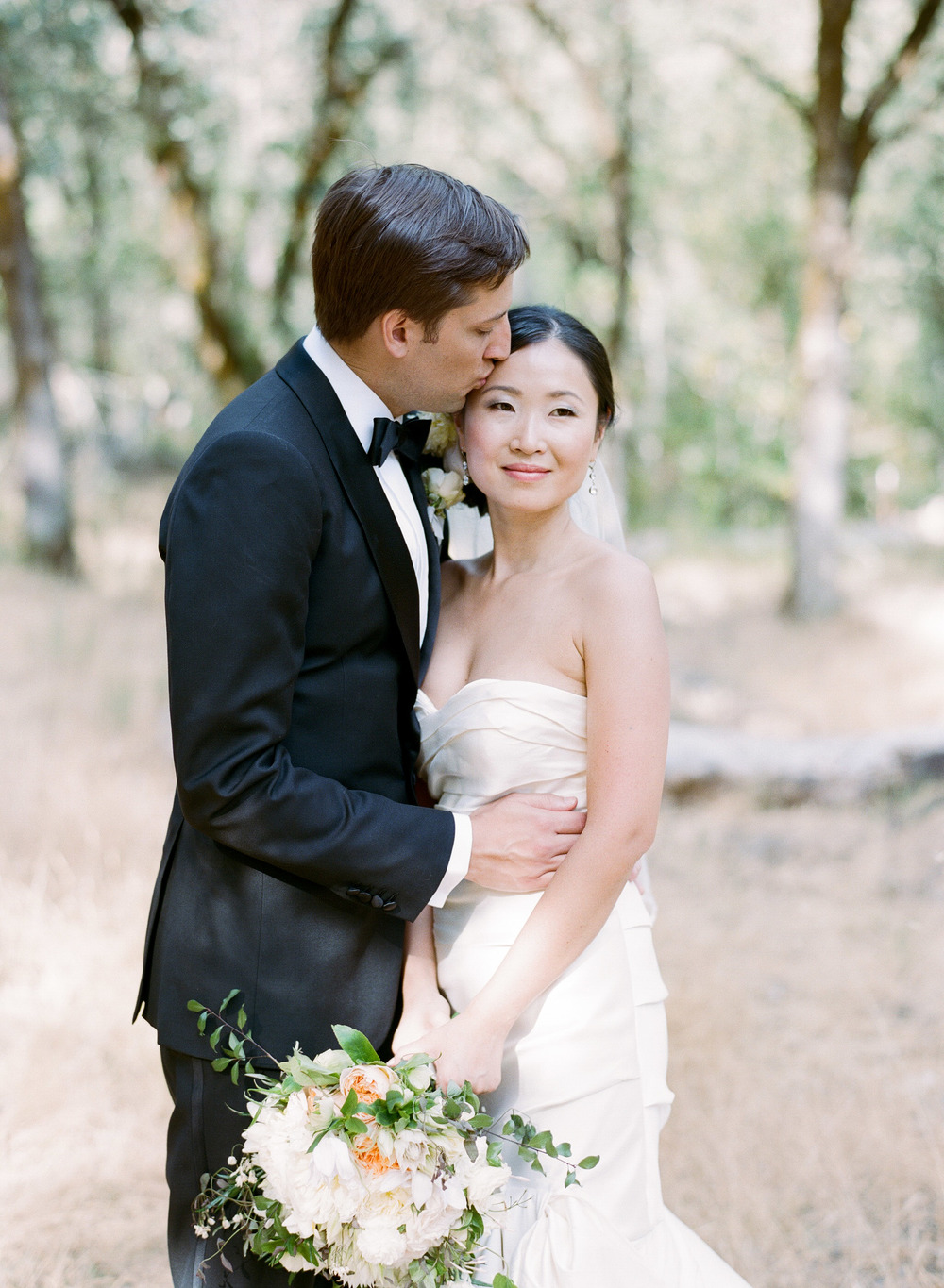 Newly married bliss - Peter kisses his new wife as the pair stand together for a couple shoot in the woods of Napa Valley; photo by Sylvie Gil
