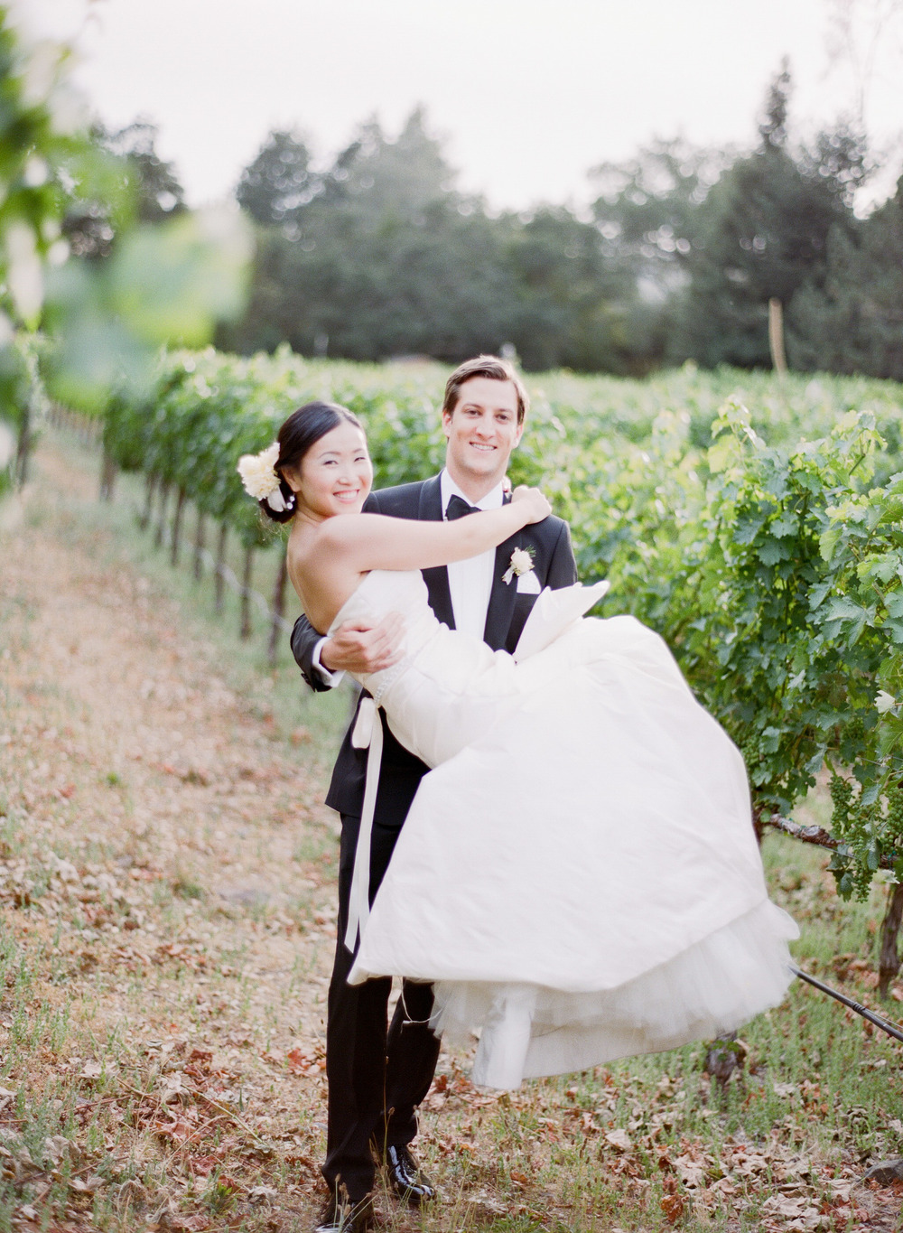 A new husband carries his bride through a Napa vineyard during a couple session with Sylvie Gil