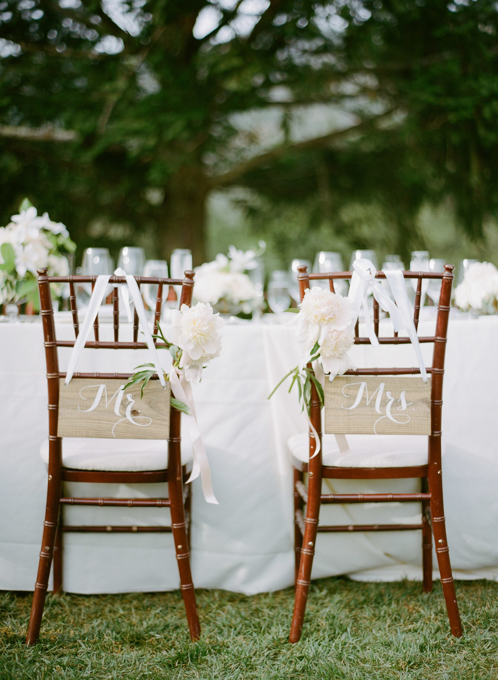 The couple's seats at the ceremony are decked out with Mr. & Mrs. signs and ethereal floral designs; photo by Sylvie Gil