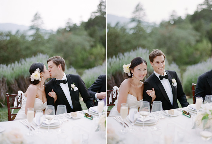 Di and Peter share a kiss seated at the long reception table at their lovely outdoor Calistoga Ranch wedding reception