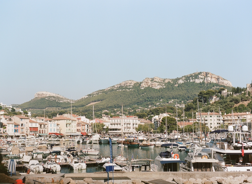 A cityscape in Provence by a boat-filled marina with craggy hills in the background; photo by Sylvie Gil