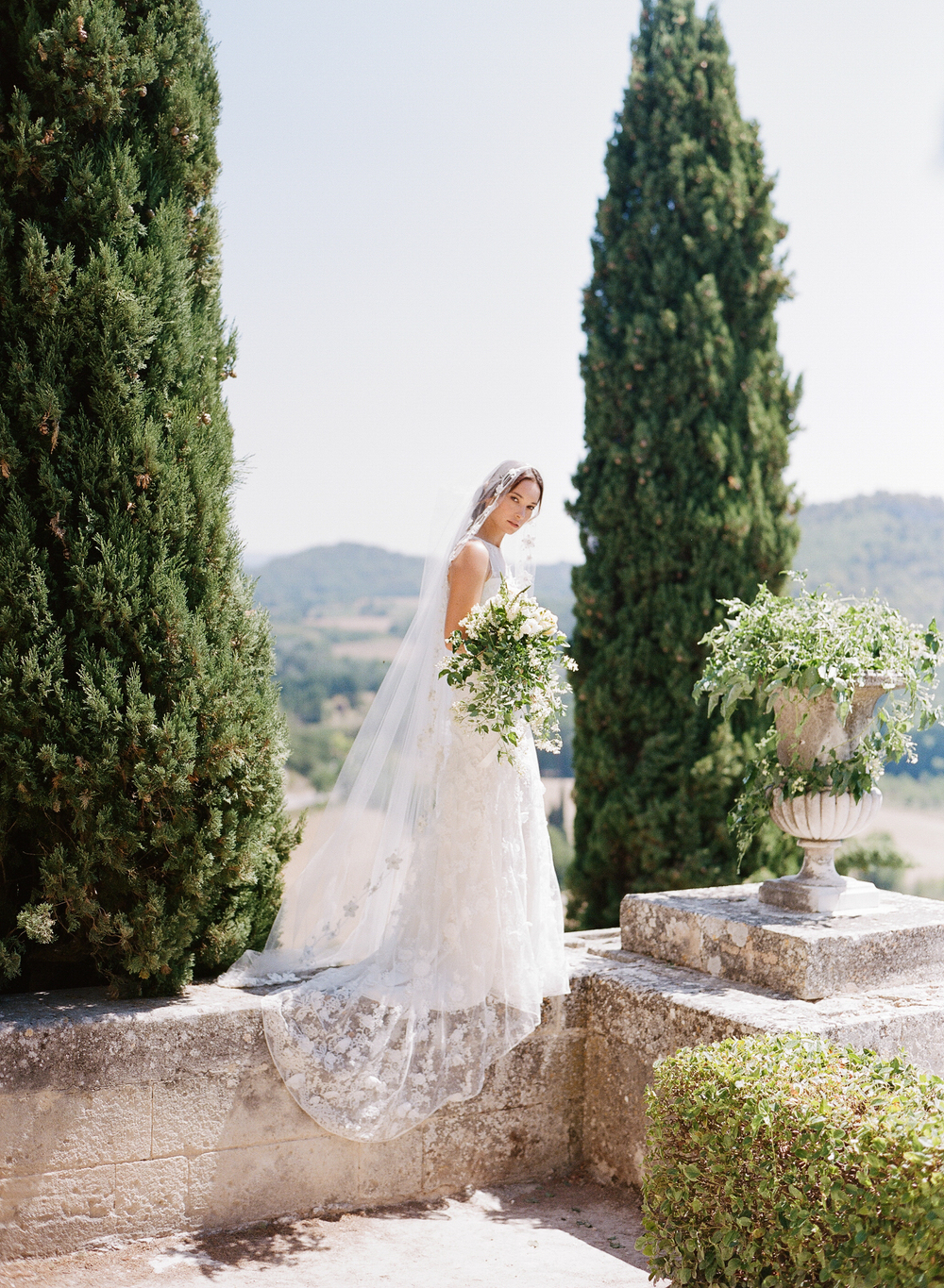 The bride stands on a terrace wall in the chateau in Provence, wearing a Claire Pettibone gown and veil; photo by Sylvie GIl