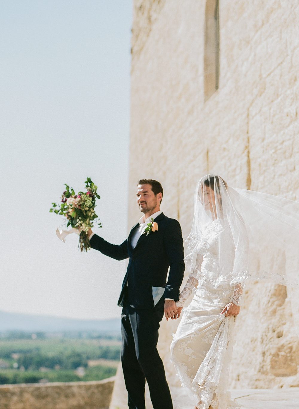 Bride and groom walk hand in hand down the church steps, just married in this quaint Provençal village; photo by Sylvie Gil