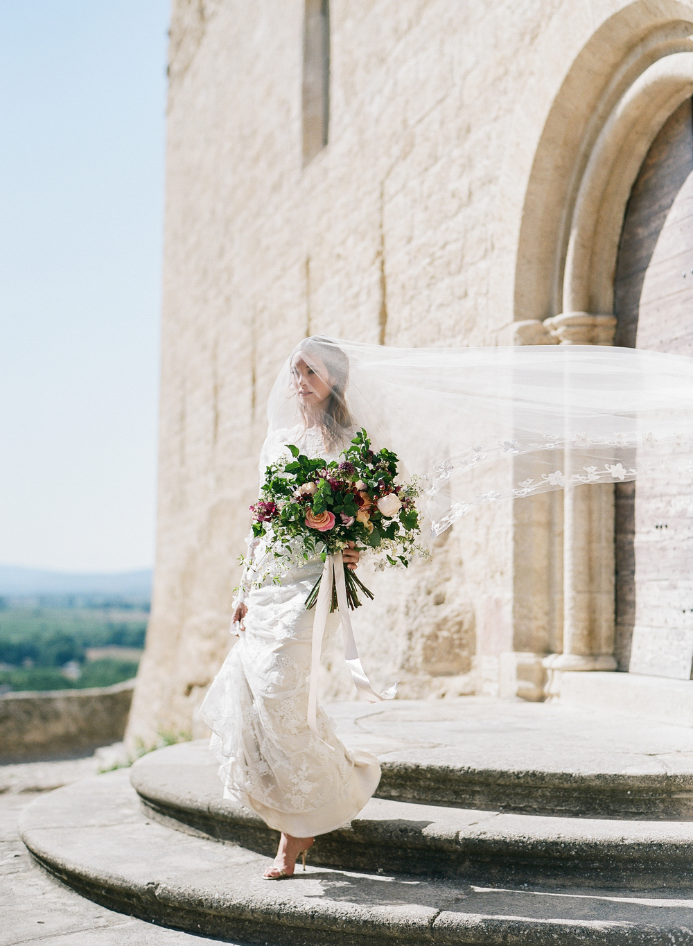 The bride holds a large, rustic, colorful bouquet, and walks down the church steps with her lace Claire Pettibone veil streaming behind her in the wind; photo by Sylvie Gil