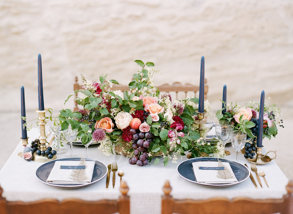 The intimate reception table set for four in the chateau courtyard features a rustic centerpiece spilling over with black grapes and figs as well as navy and gold themed place settings; photo by Sylvie Gil