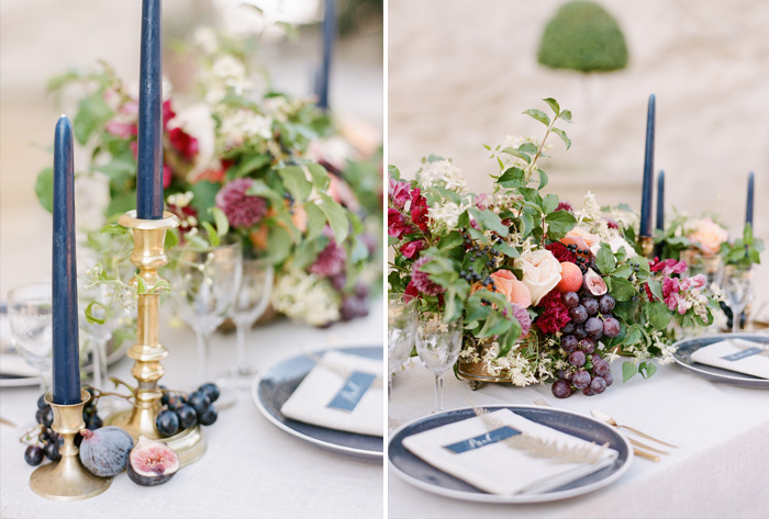 Navy and gold place settings match tall candlesticks paired with grapes and figs for the table as well as a rustic centerpiece; photo by Sylvie Gil