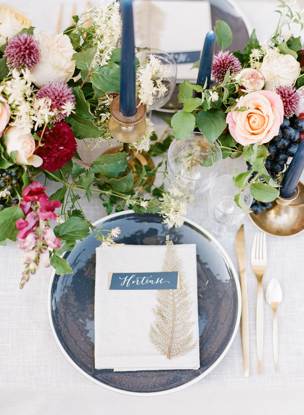 A monogrammed place setting features elegant gold details on a navy plate, surrounded by rustic, colorful place settings; photo by Sylvie Gil