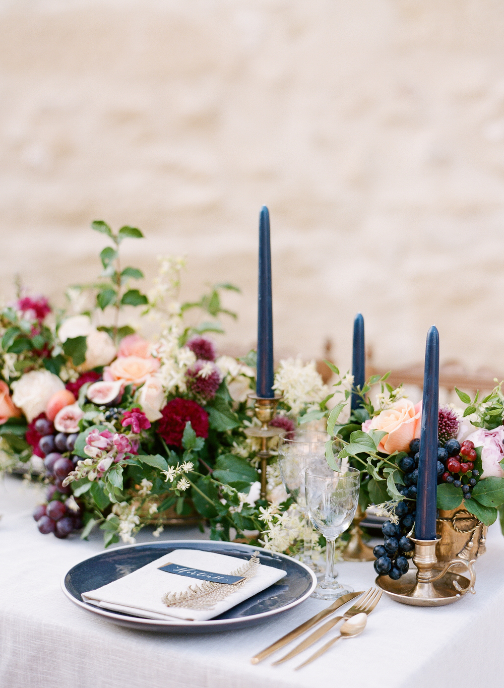 Navy and gold place settings compliment a relaxed and rustic centerpiece featuring colorful florals and fruits; photo by Sylvie Gil