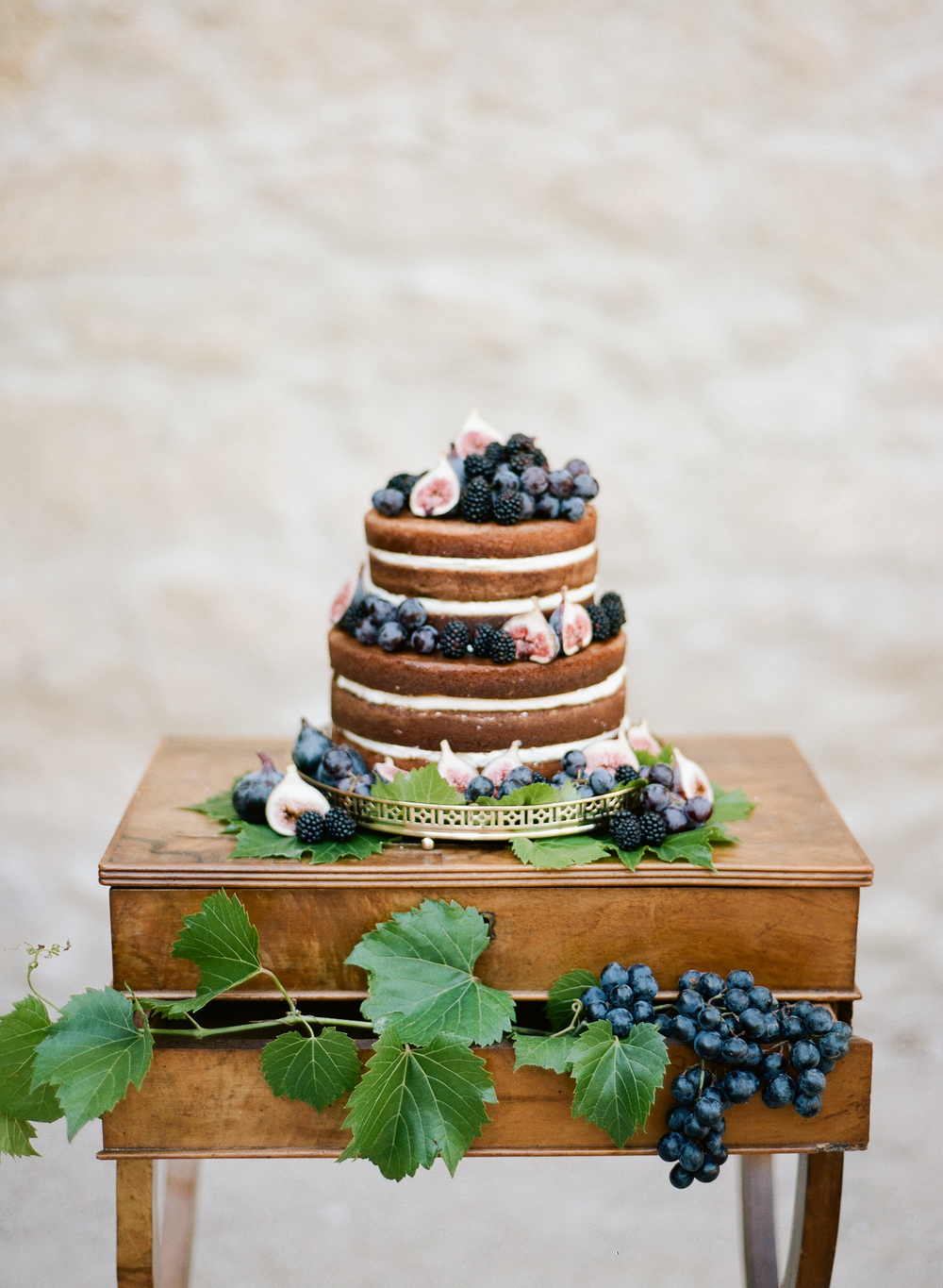 A naked cake topped with blackberries, figs, and grapes compliments the rustic elegance of the Provençal chateau wedding; photo by Sylvie Gil