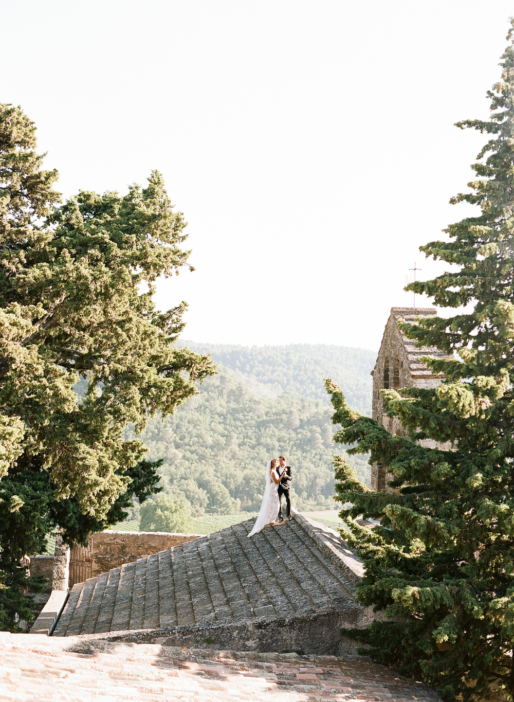The bride and groom embrace on a church rooftop in a rustic Provençal village during the sunset; photo by Sylvie Gil