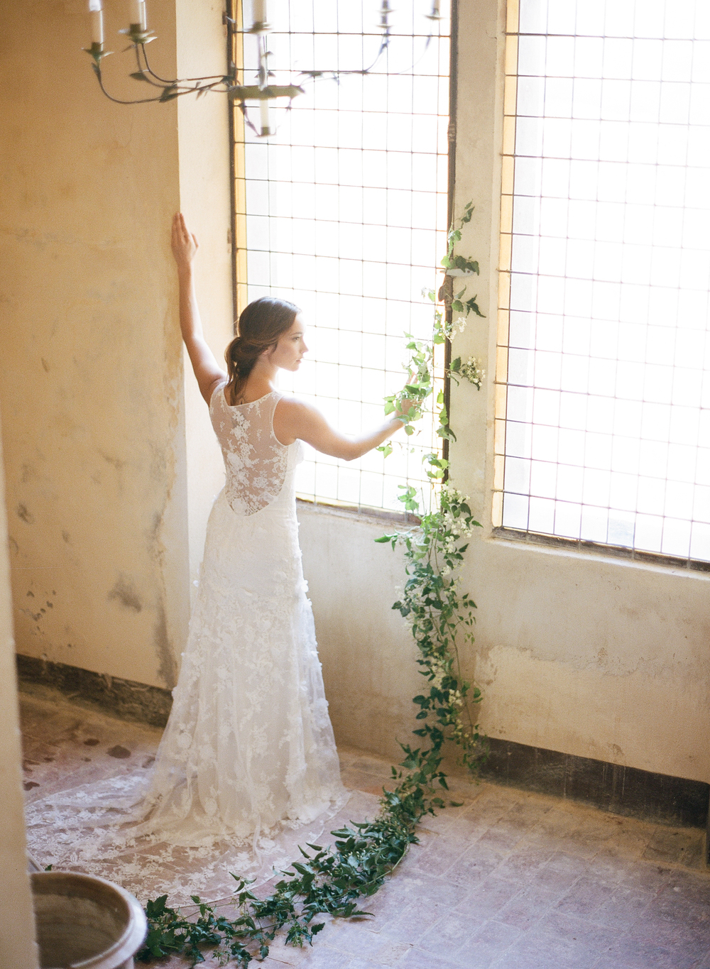A trailing vine decorates the window where the bride stands, dressed in an elegant lace Claire Pettibone gown; photo by Sylvie Gil