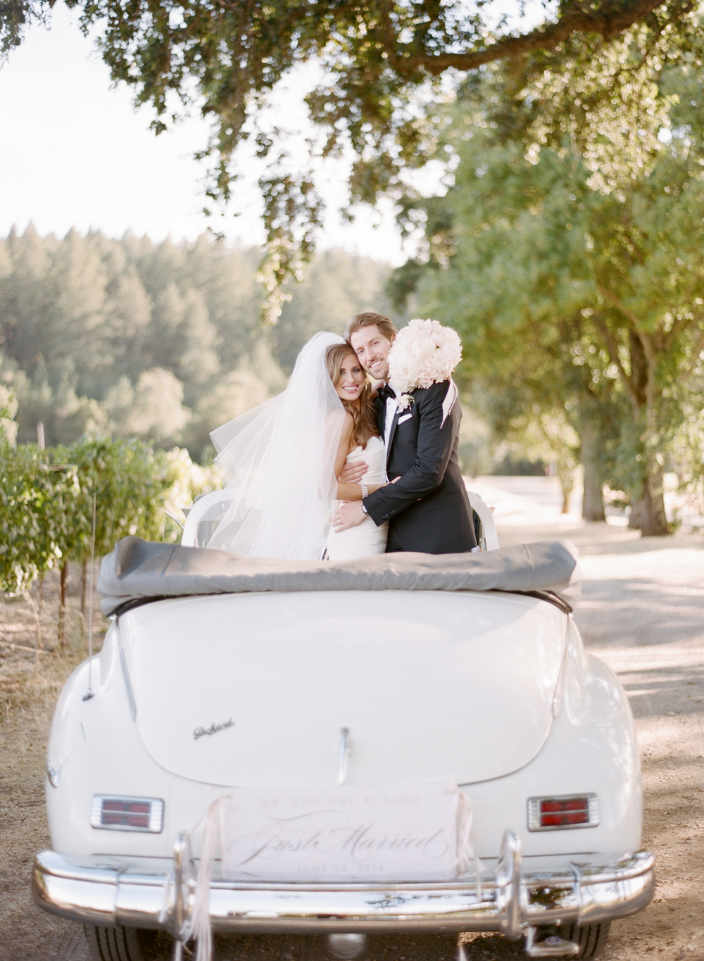 Lauren & Michael embrace, standing in a vintage white car in a winery during a couple shoot with Sylvie Gil