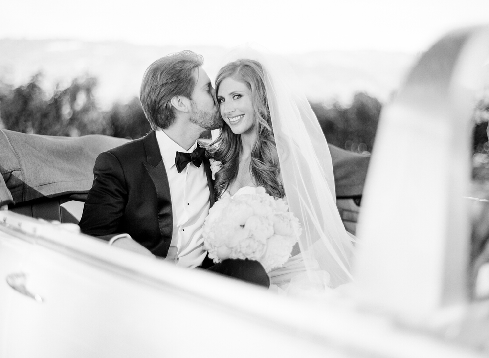 Michael kisses his bride in the backseat of a convertible vintage car during a just-married couple shoot with Sylvie Gil