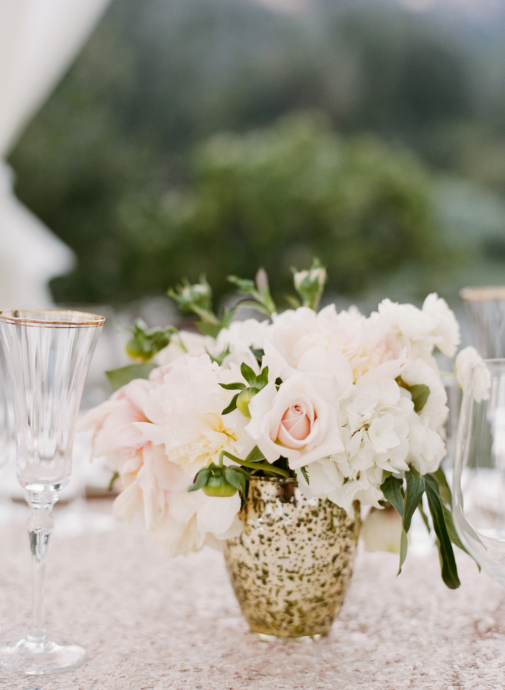 A gorgeous blush centerpiece arranged in a gilt vase decorates the outdoor reception table; photo by Sylvie Gil