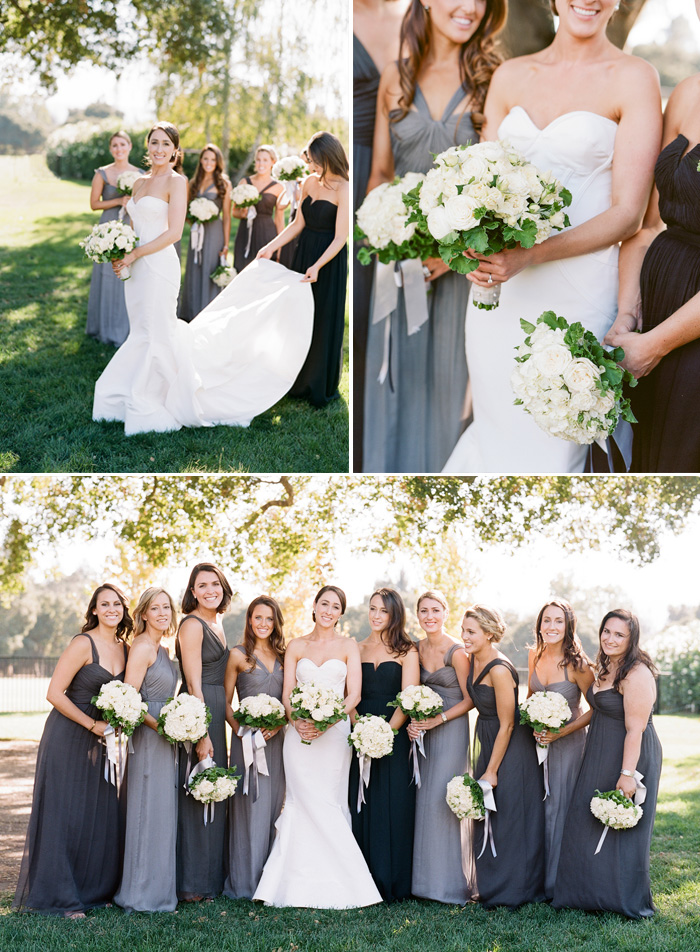 Nine bridesmaids in gray, navy, and black pose with the bride, dressed in a stunning Oscar de la Renta gown with a sweetheart neckline; photo by Sylvie Gil