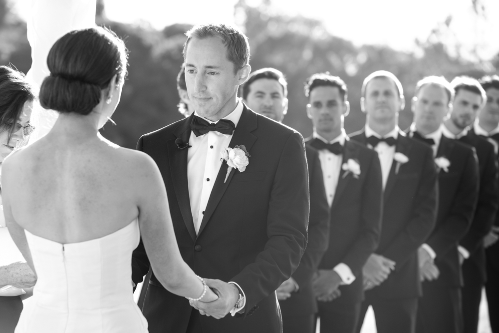 The bride and groom hold hands and exchange vows as the groomsmen look on; photo by Sylvie Gil