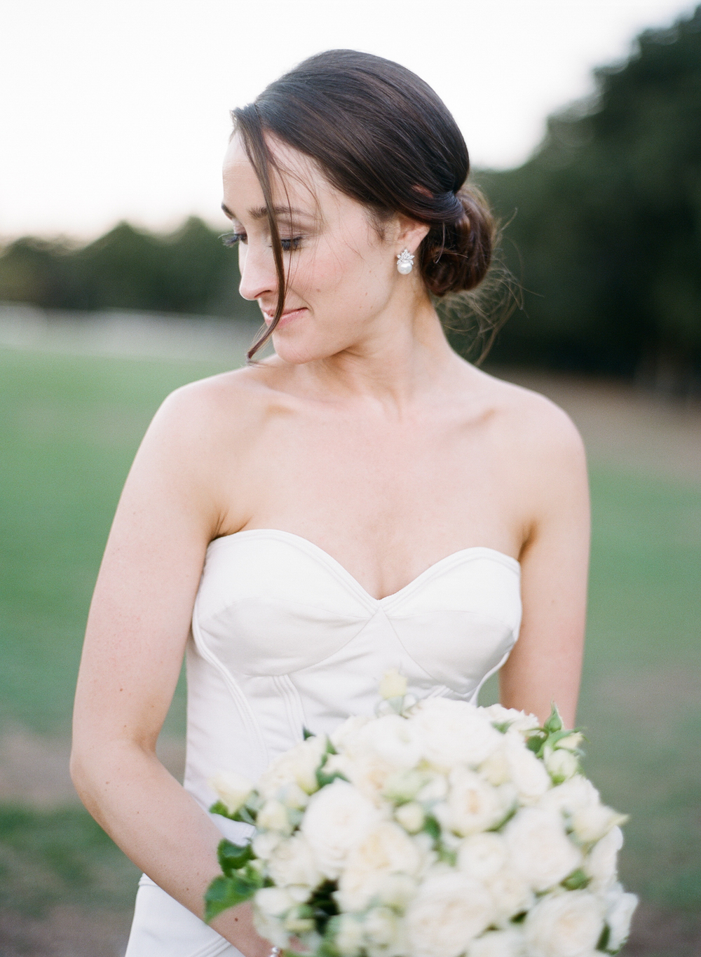 A classic bride looks away, wearing a gorgeous Oscar de la Renta gown; photo by Sylvie Gil