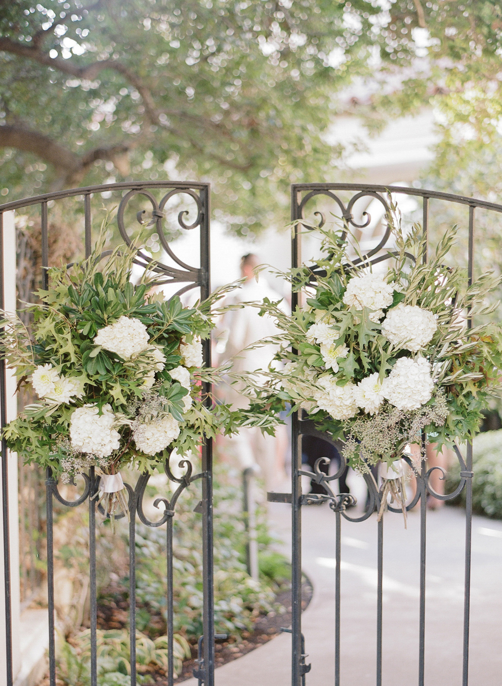 Accent floral wreaths hang on a wrought iron gate outside the ceremony; photo by Sylvie Gil