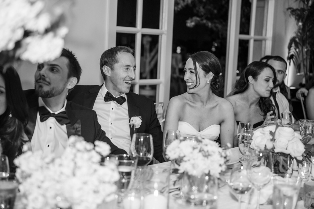 The bride and groom share a smile during the reception party indoors; photo by Sylvie Gil