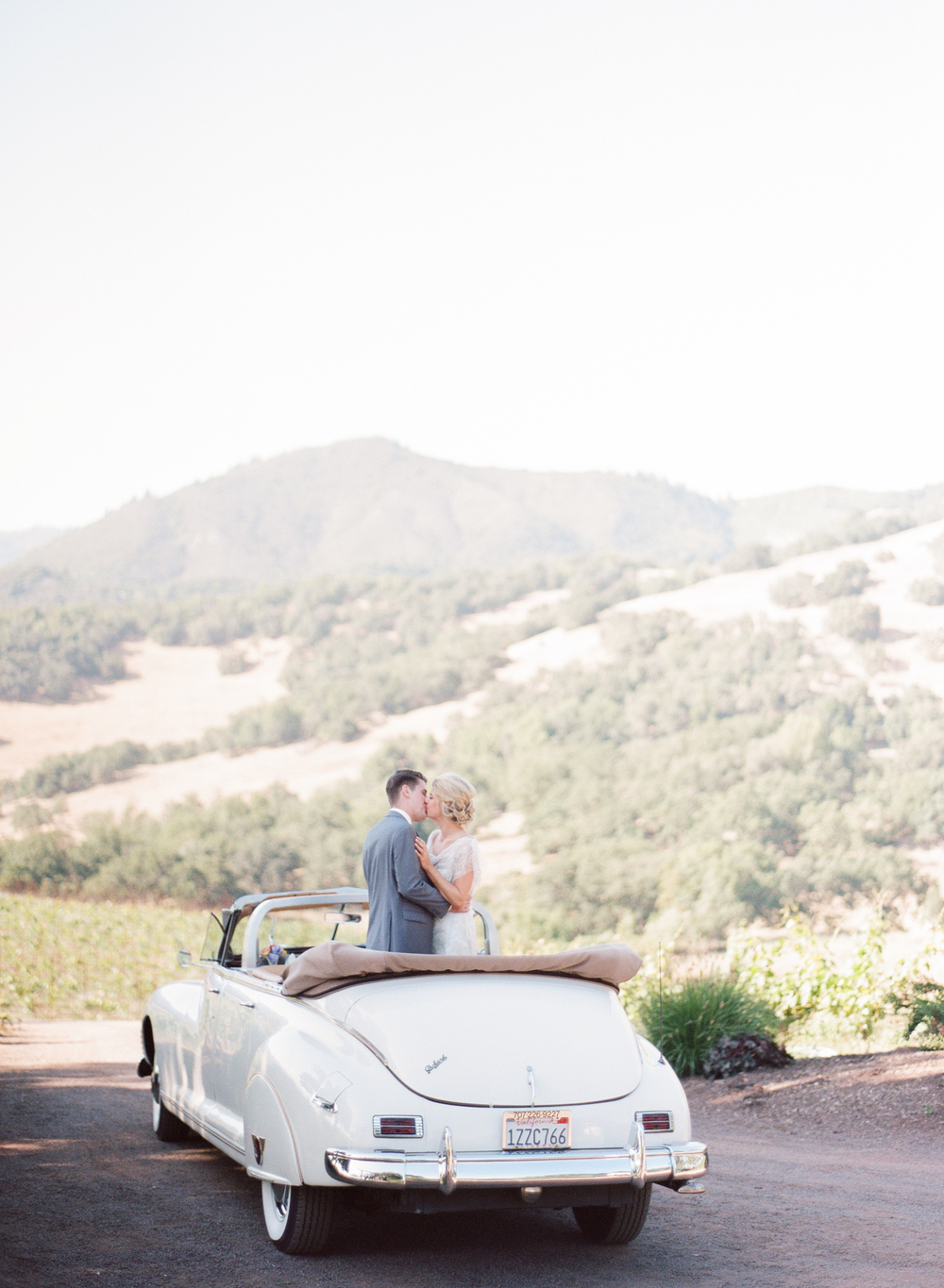 Whitney and Justin pose in a vintage convertible in California wine country for a couple shoot with Sylvie Gil
