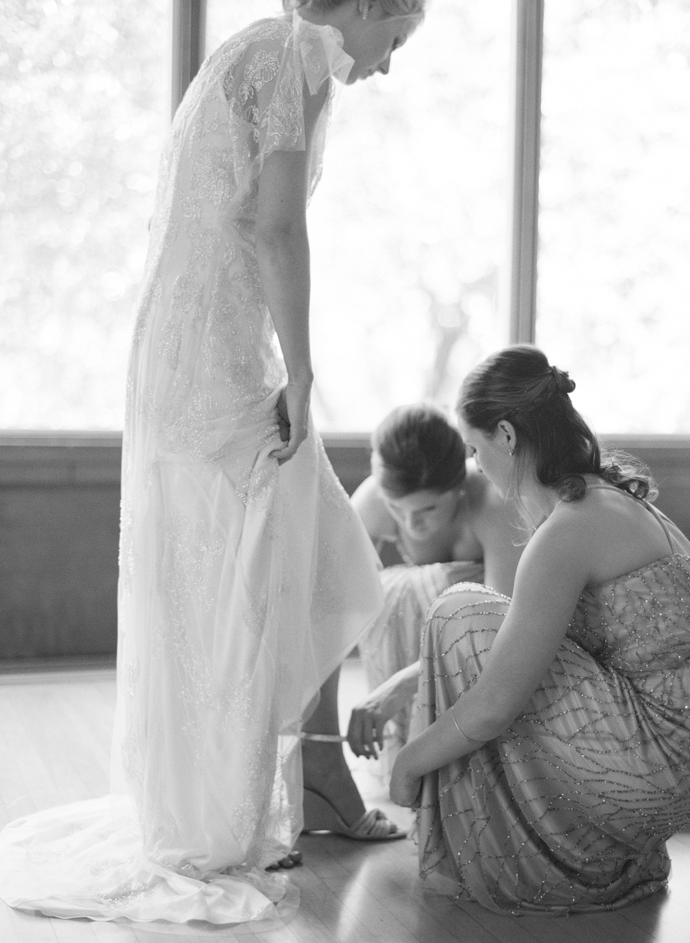 Whitney, dressed in an elegant sheath dress steps into her shoes held by her bridal party while getting ready; photo by Sylvie Gil
